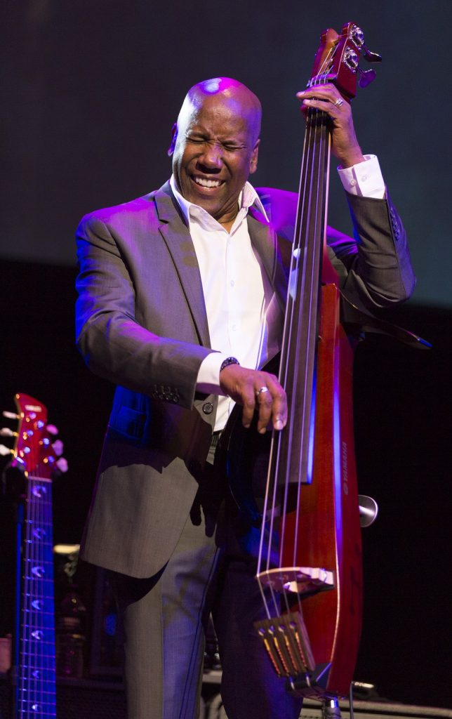 Man in a suit smiling while he plays an electric upright bass (EUB).