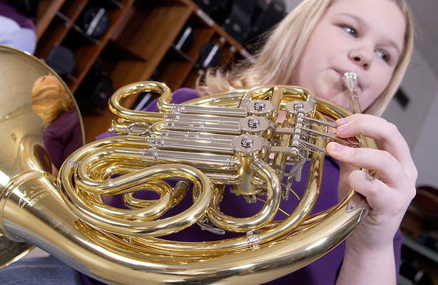 Closeup of French horn being played by a young blonde woman.