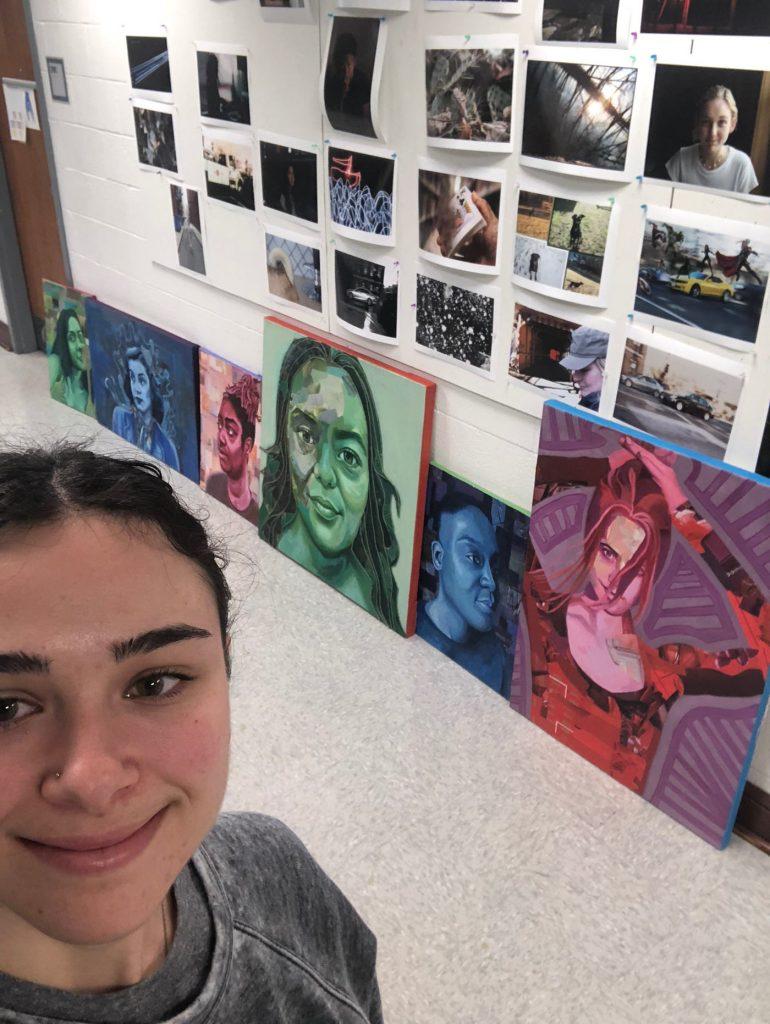 Smiling young woman in front of a wall full of original art.