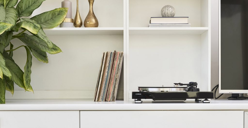 Turntable on a shelf next to a flat screen and a row of vinyl albums in their dust covers, plus other decorative items on the shelves above.