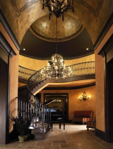 Entry way to a grand home with soaring ceilings and a dome with a chandelier. There is a curving staircase from main floor to upper level in background. Tucked into the large alcove created by the curving staircase and under overhang of second floor is a grand piano with lid open.
