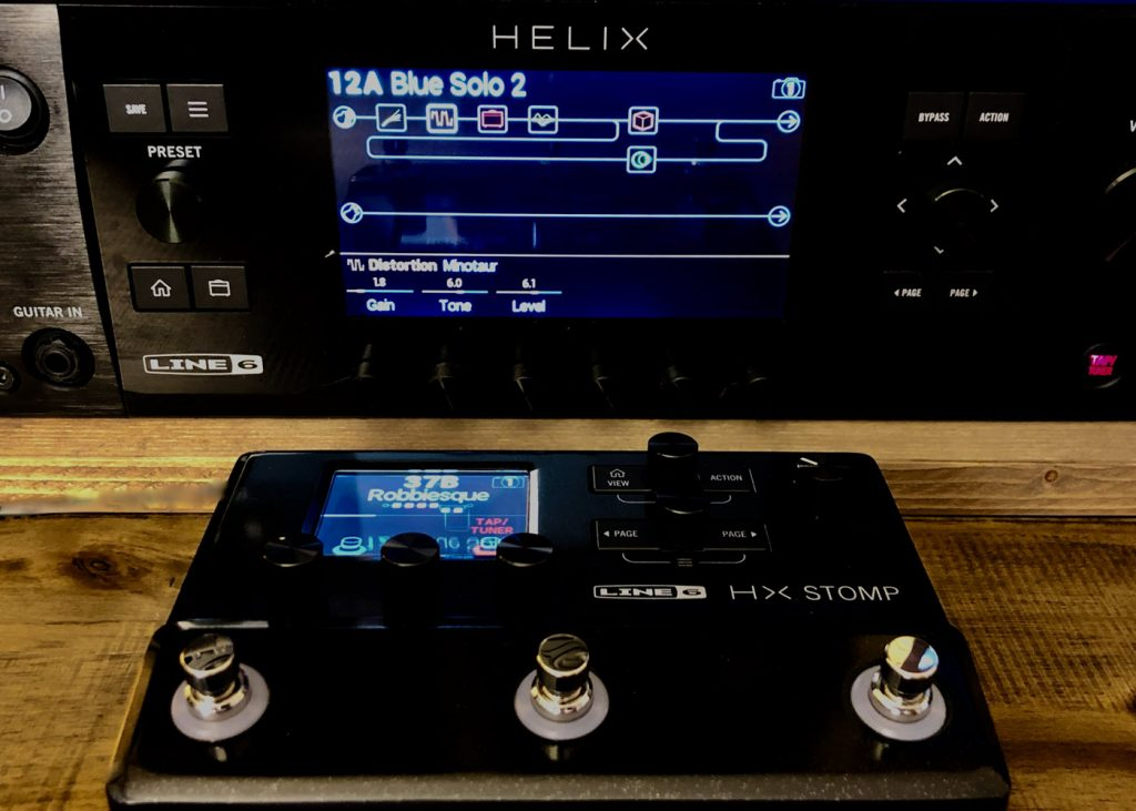 """Small electronic controller with three toggle switches and a small screen in foreground and a larger electronic element in background with many controls and a screen displaying a flowchart and the words """"Helix"""" and 12A Blue Solo 2""""."""