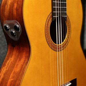 Closeup of the body of an acoustic guitar with three knobs on side for reverb, volume and chorus.