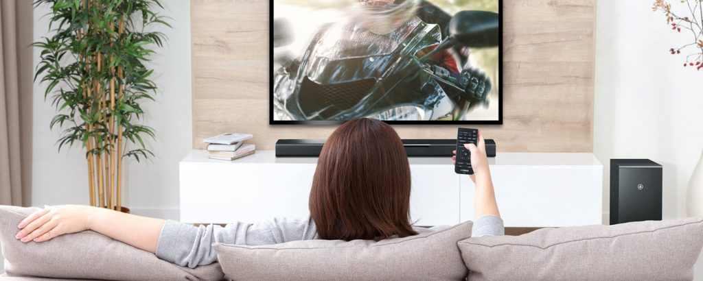 View from behind of a woman sitting on a couch watching tv with remote in her hand and a soundbar directly below the tv on the far wall.