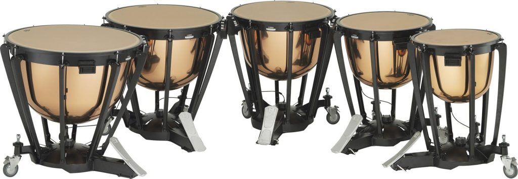 Set of 5 timpani drums in a curved row.