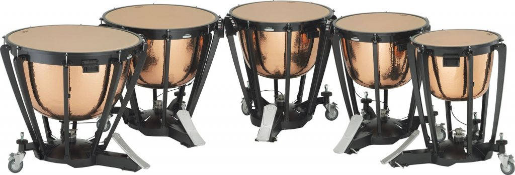 Set of 4 timpani drums in a curved row.