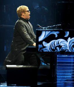 Elton John in concert singing at a piano