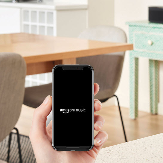In a room where there is a table and chairs in background, you see a hand holding a smartphone with the screen showing the Amazon Music logo.