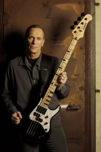 Tall slim man in his 40's holding a bass guitar.