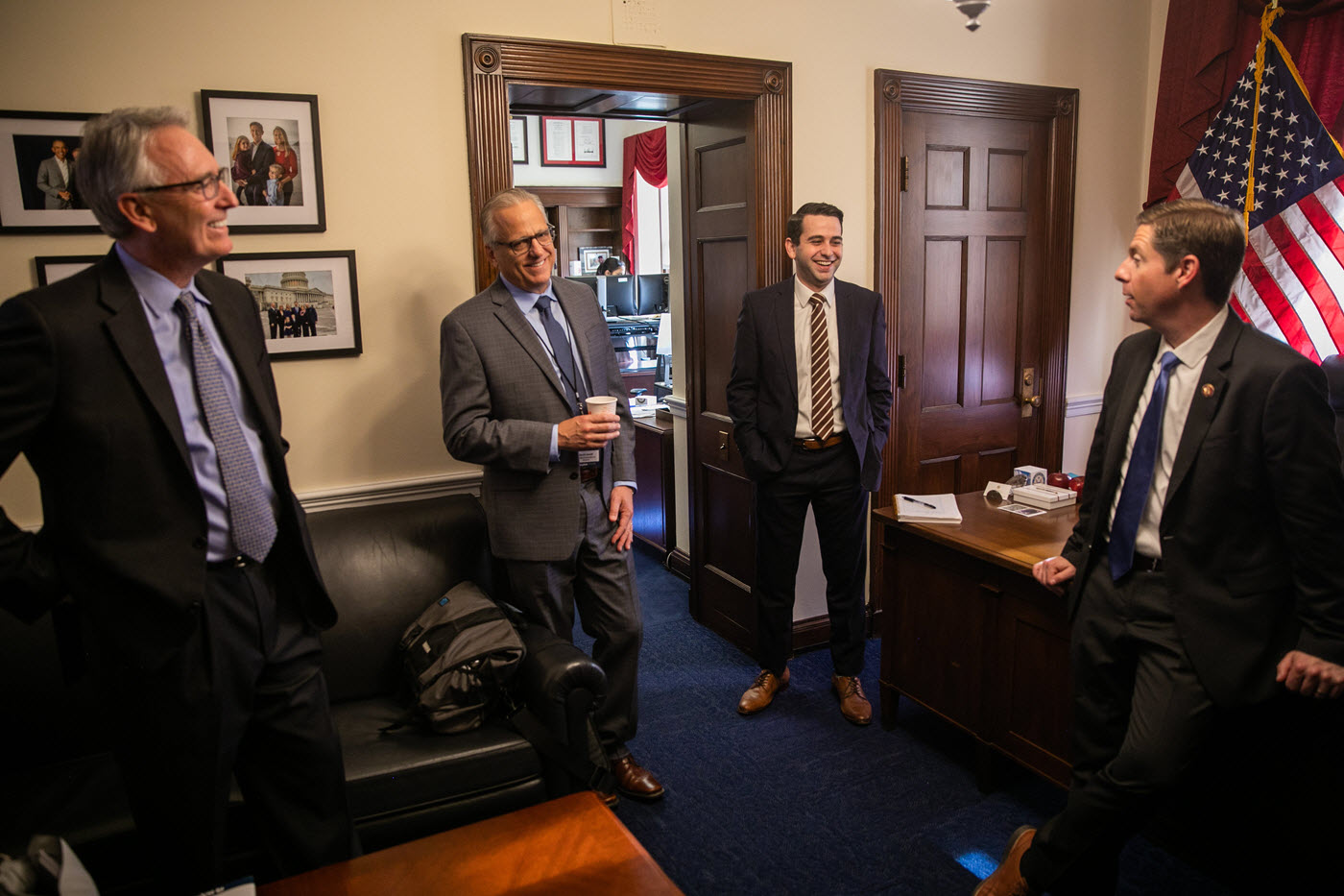 Four men in suits standing in an office laughing and talking.