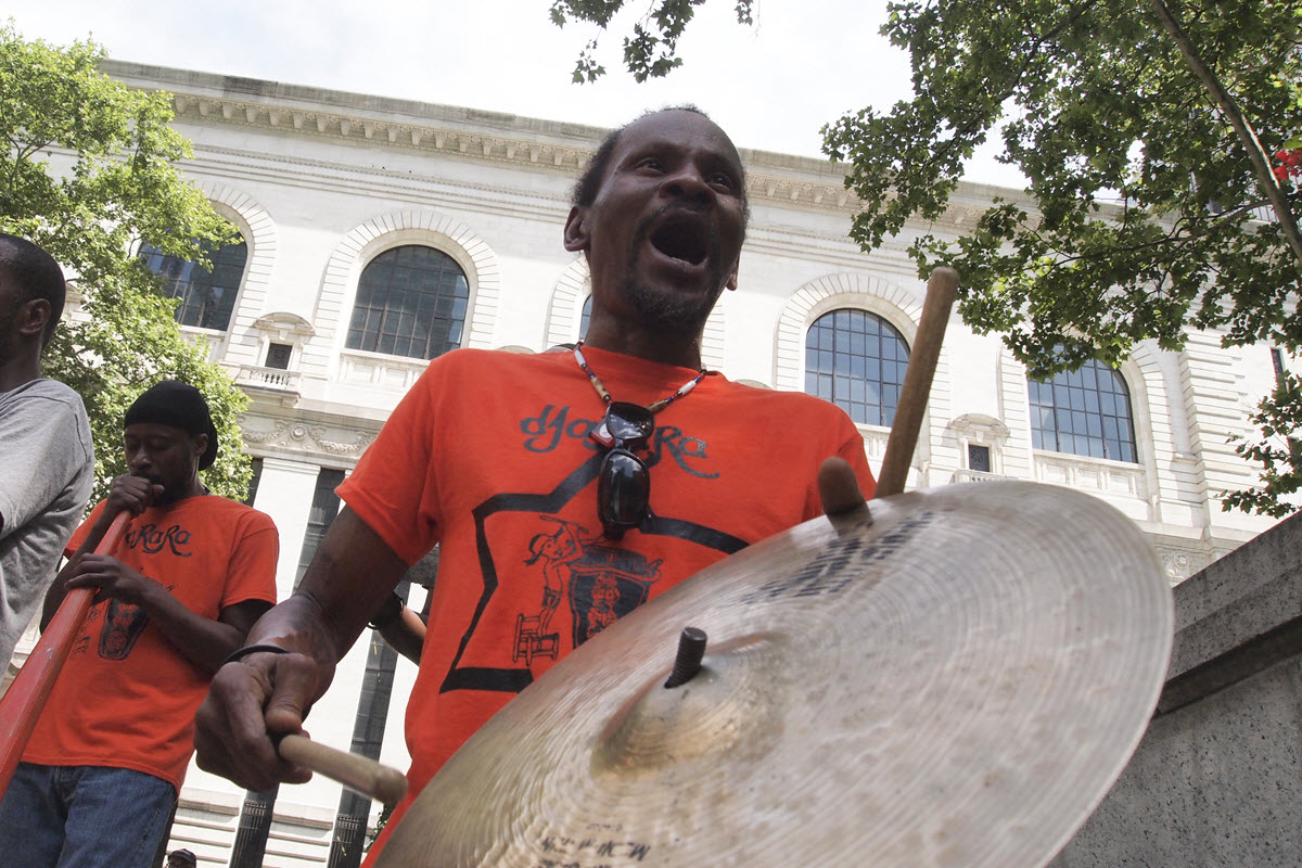 Group of men in matching t-shirts playing instruments on the street. Man in foreground is playing a large cymbal. Man in in background is playing some form of a horn.