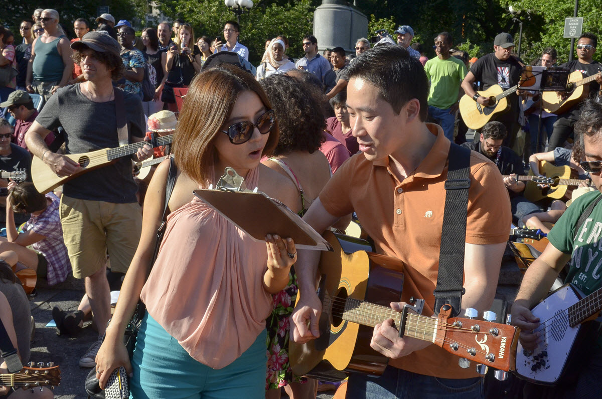 Large gathering of people on a sidewalk in front of a park playing acoustic guitars and singing.