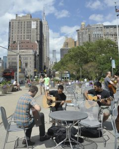 Group of young men sitting at a sidewalk cafe playing acoustic guitars while others in background watch and listen.