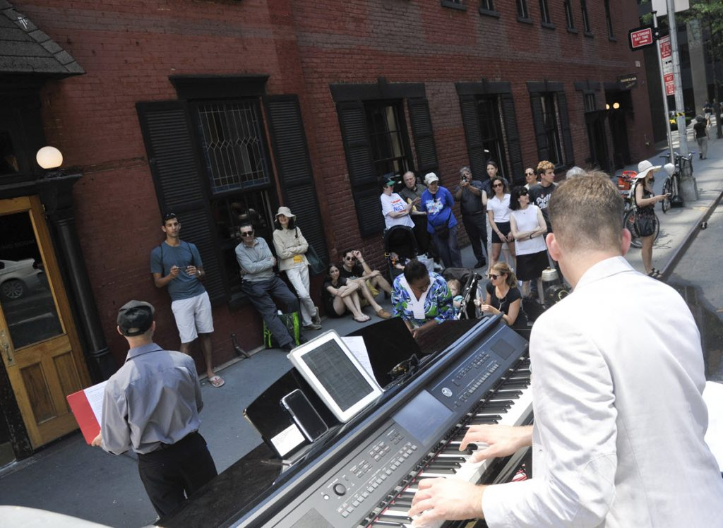 Singer accompanied by electronic piano performs for a group of people on a sidewalk in front of a large brick building.
