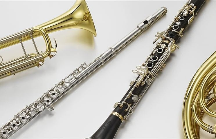 Four instruments laying side-by-side on a table, a gold trumpet, a silver flute, a black wood clarinet and a brass French horn.