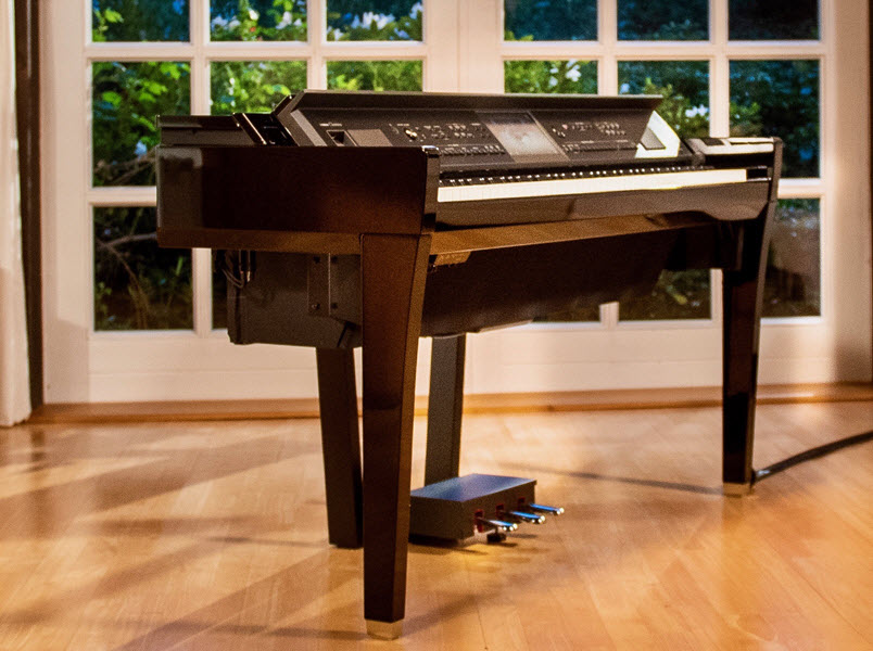 Electronic baby grand piano in the center of an upscale living room with hardwood floors, french doors in the background.