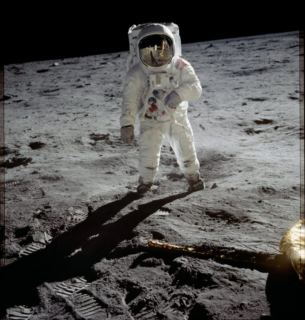 Person in space suit and helmet standing on sanding desolate surface.