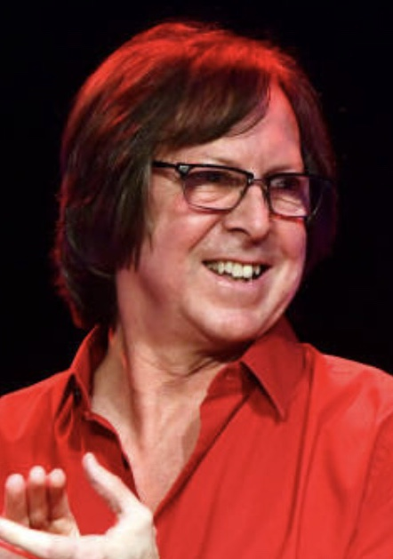 Man in glasses smiling and applauding while looking over his left shoulder.