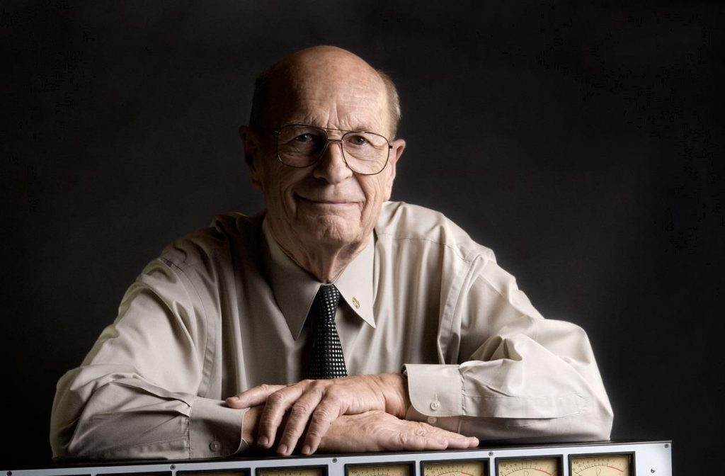 Older man in shirt and tie with his forearms resting on an older version of a sound board.