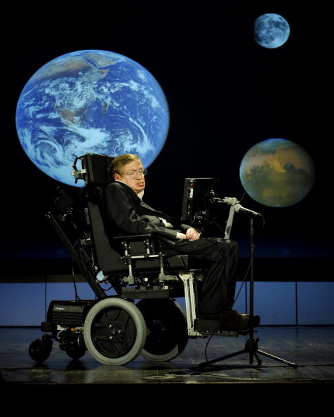Man in a suit slumped down in an electric wheelchair with a computer screen in front of him and images of Earth and other planets projected in the background.