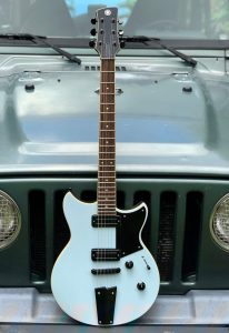 Electric guitar standing on a bumper of a jeep.