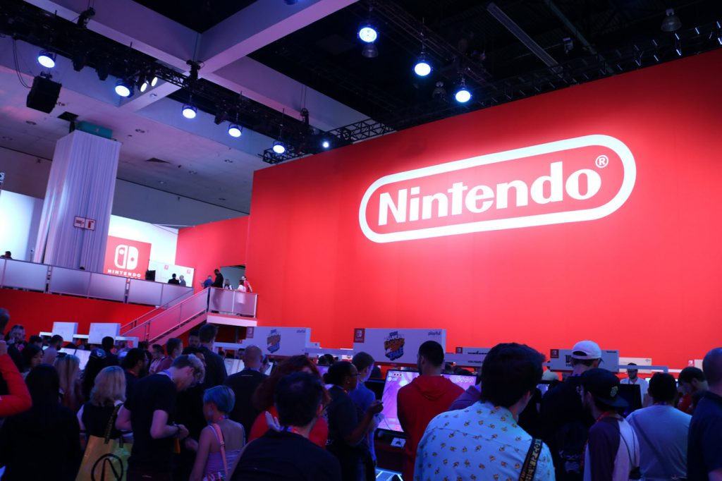 Dense crowd clustered in front of a large tradeshow booth with an enormous Nintendo logo on wall in background.