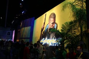 "Large crowd clustered in front a large wall where a graphic image of a young man holding a gun and the title ""CyberPunk 2077"" is emblazoned."
