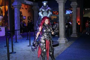 "Young woman dressed in a costume emulating the futuristic armor and weaponry of the ""Darksiders Genesis"" statue behind her."