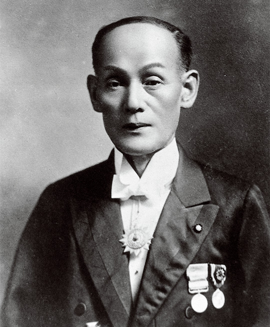 Photo of a Japanese man in a tuxedo which is adorned with various medals.