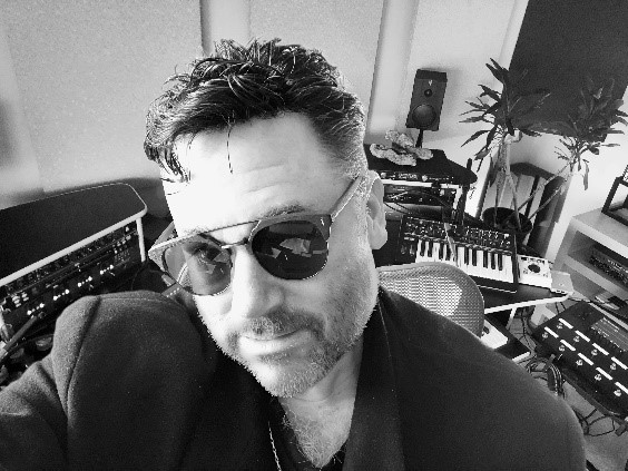 Man in sun glasses sitting at mixing console.