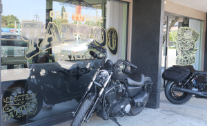 Viewed from outside, the front windows of the Old Towne Tattoo Parlor with two Harley Davidson motorcycles parked on the sidewalk directly in front.
