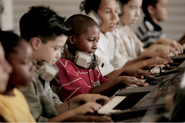 Row of children playing keyboards with headsets around necks.