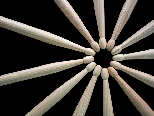 A group of drumsticks arranged with tips pointing towards each other forming a circle.