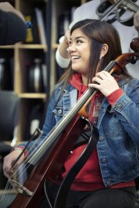 Teenage girl in casual clothes playing an upright electric bass in a bandroom setting.