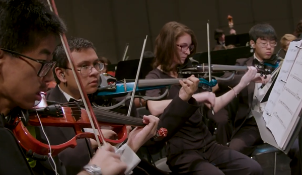 Teacher in a middle school music class showing kids how to play electric violins. There are three students in image focused on playing from sheet music.