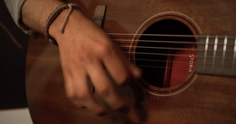 """Closeup of a hand playing an acoustic guitar. Through the guitar hole, there is a label with the name """"Storia""""."""