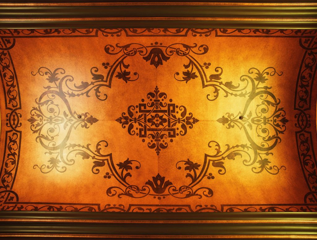 A ceiling painted to look like inlaid antique wood with an intricate scrollwork design.