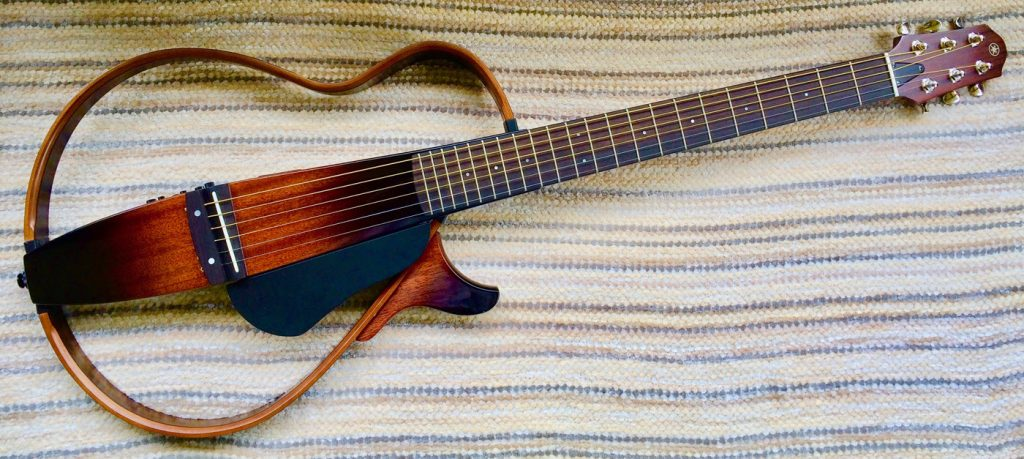 An acoustic guitar with an entirely open body laid on a striped woven cloth.