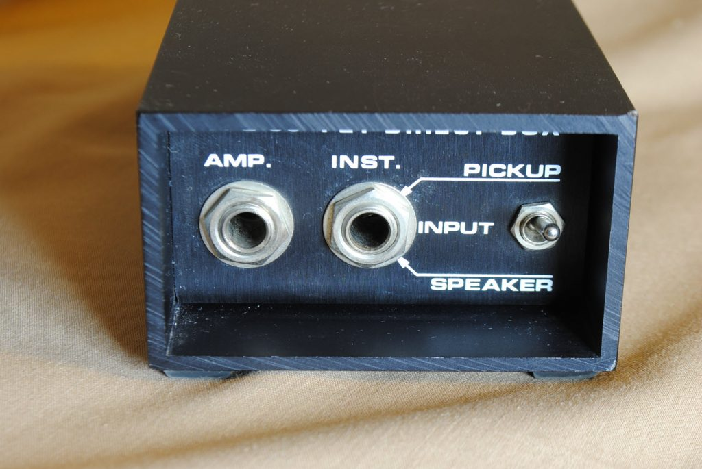 """Closeup image of a direct input or """"DI"""". There are two female inputs and a toggle switch."""