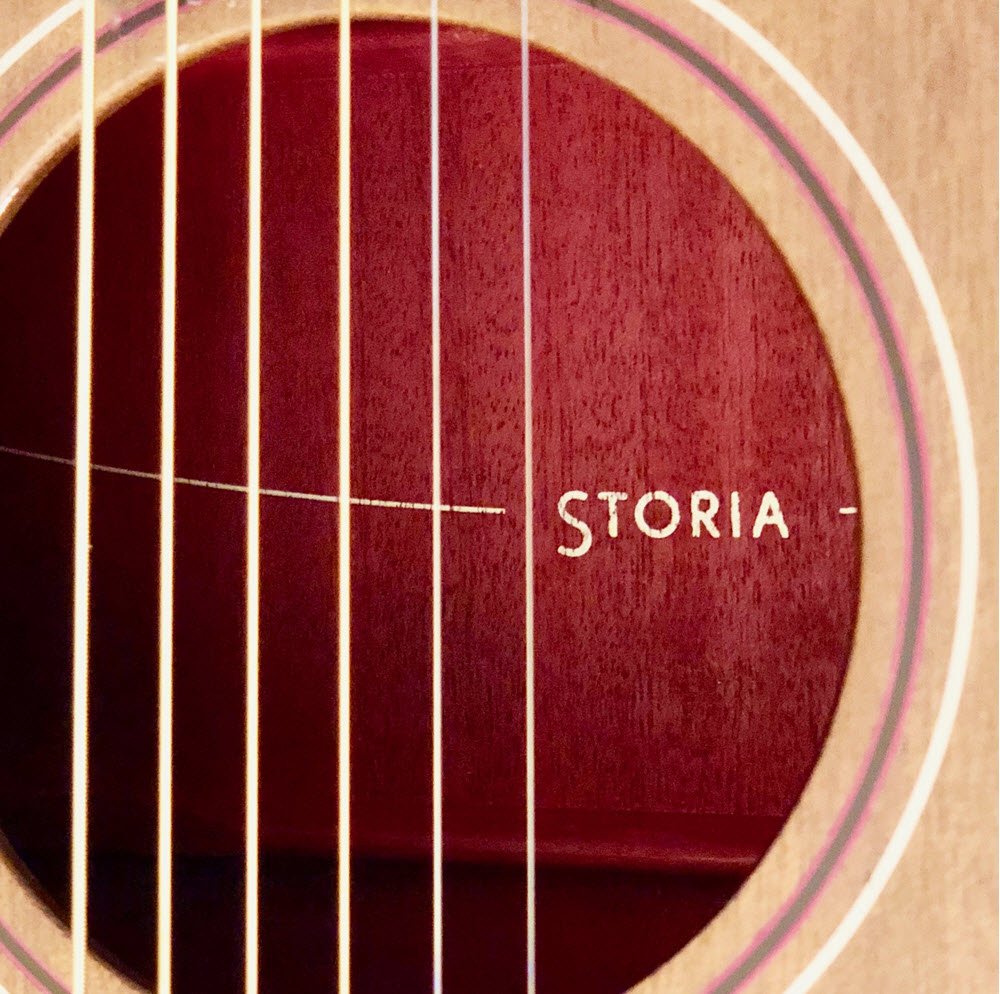 "Closeup of the inside of an acoustic guitar through the strings into the hole. The word ""Storia"" is on the inside back wall of guitar."