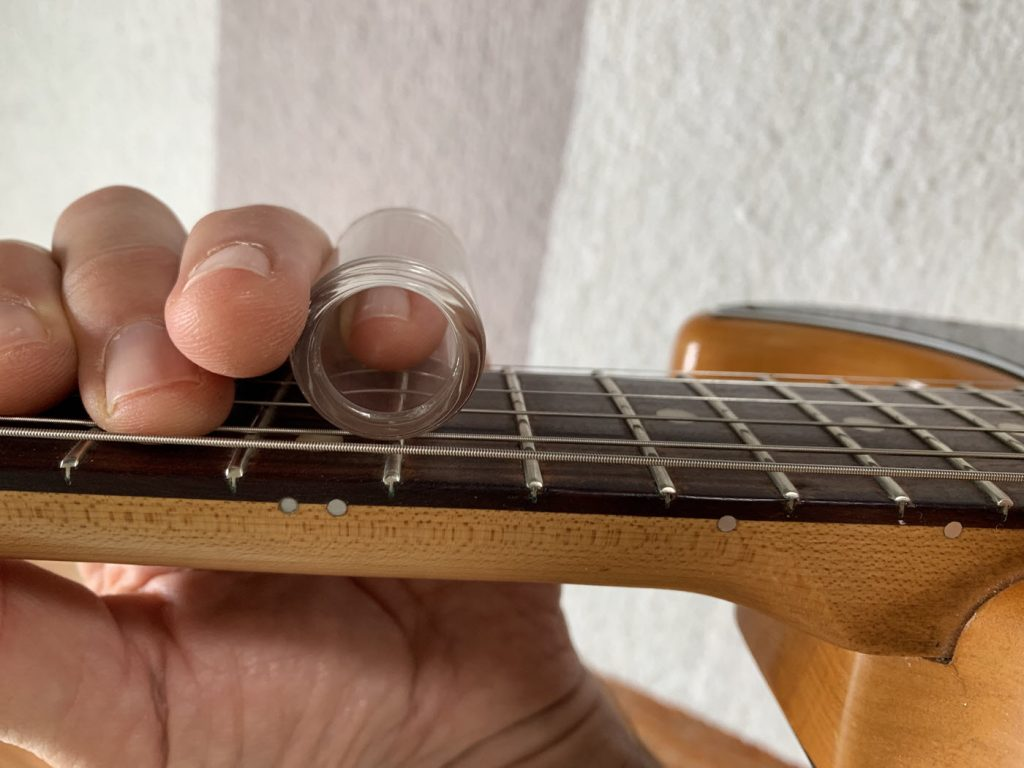 "Closeup of a hand on the neck of a guitar. They are wearing a glass tube on the index finger against the strings right over one of the horizontal metal bars or ""frets"".."