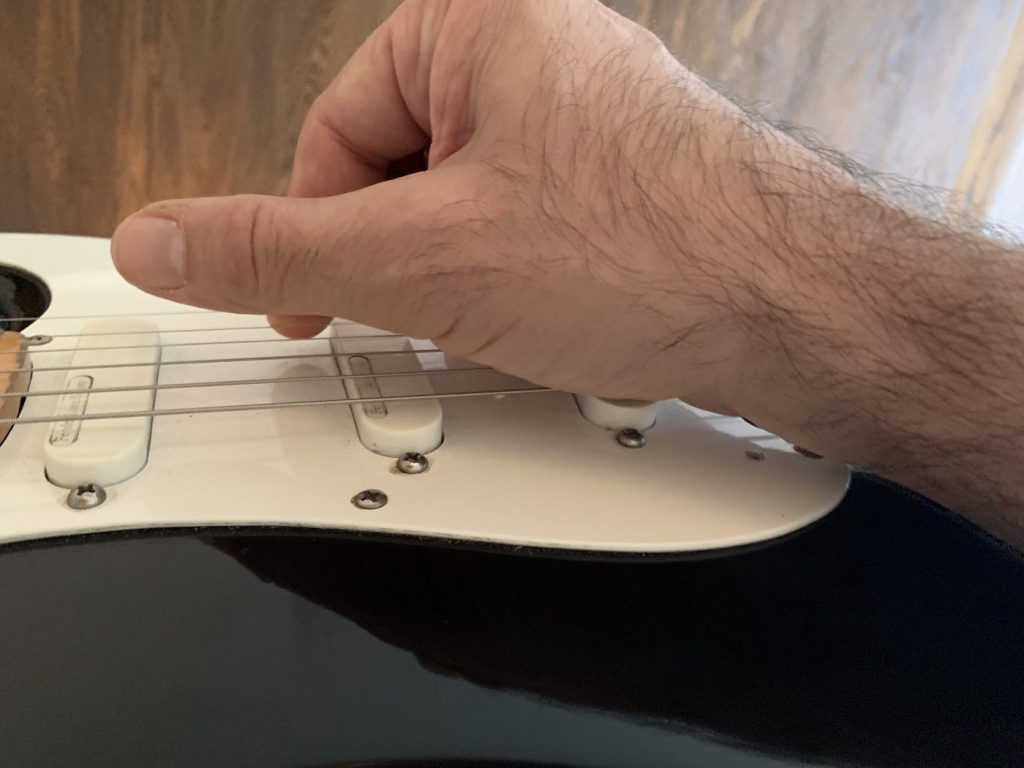 Closeup of a man's hand plucking a string on an electric guitar.