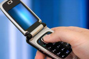 Closeup of a hand pressing a button on an open flip phone.
