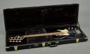 Electric bass guitar in an open hard shelled case.