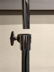 Shows the two tubes being connected where there is the one on bottom has a screw with a little handle for turning and tightening.