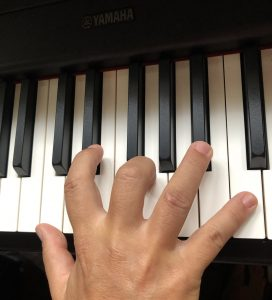 Hand on Yamaha piano keyboard demonstrating finger placement.