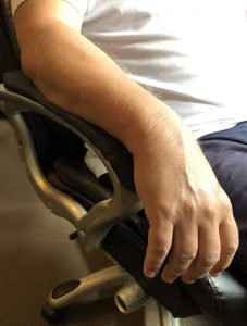 Closeup of a man's arm resting on the armrest of a rolling desk chair.