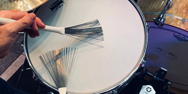 Closeup of someone playing a snare drum with brushes.