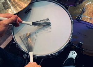 Closeup of someone playing a snare with brushes.