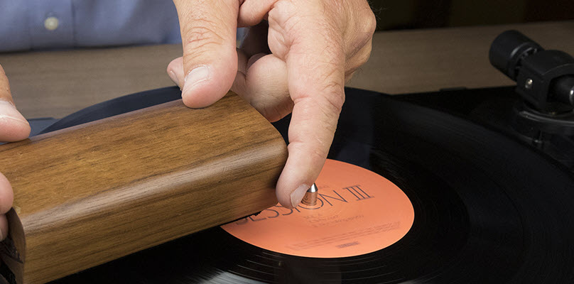Closeup of man's hands as he uses a small rectangular object to clean a vinyl record on a turntable.